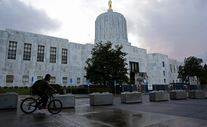 A man rides a bicycle past newly installed cement blocks that have been placed outside the Oregon State Capitol Building in Salem, Oregon on Wednesday, December 30, 2020.